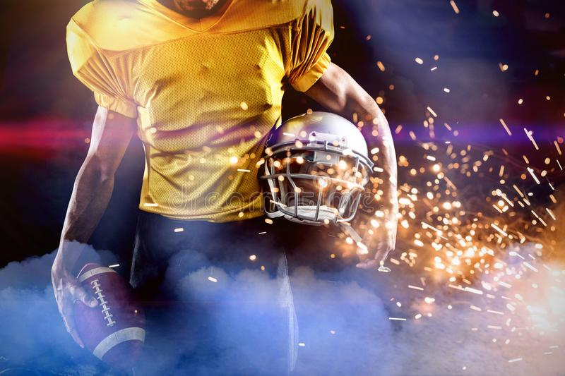 Composite image of mid section of male athlete with american football and helmet stock photo