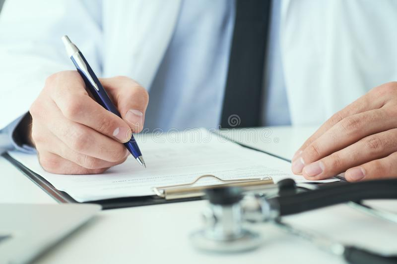 Mid section of male doctor writing write prescription to patient at worktable. Panacea and life save, prescribing royalty free stock image