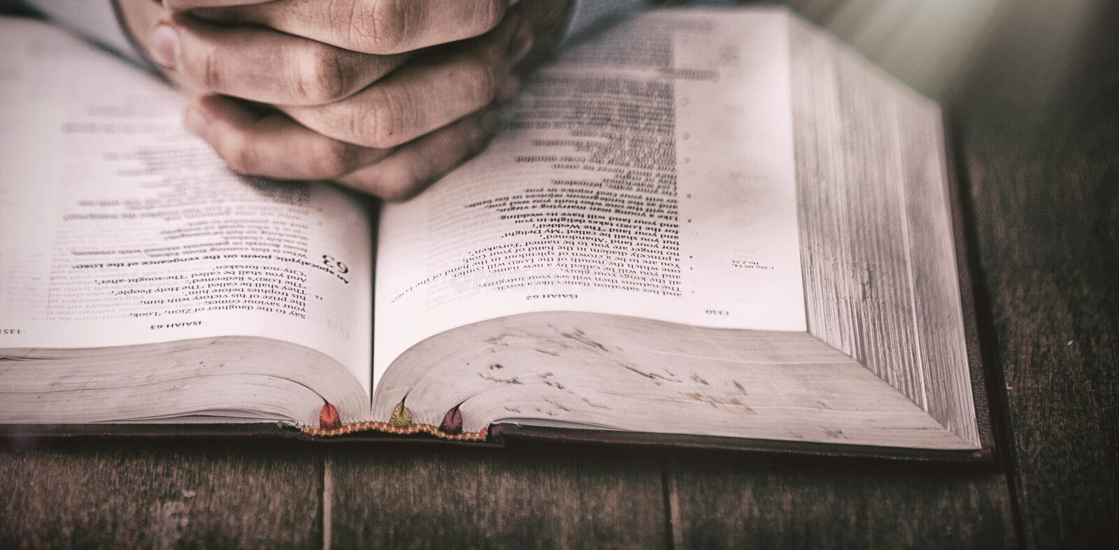 Mid section of man praying with bible. At wooden desk stock images