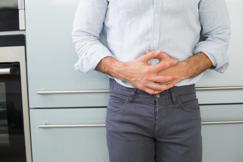 Mid section of a man suffering from stomach pain stock images
