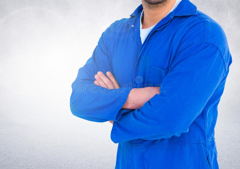 Mid section of mechanic standing with arms crossed stock photo