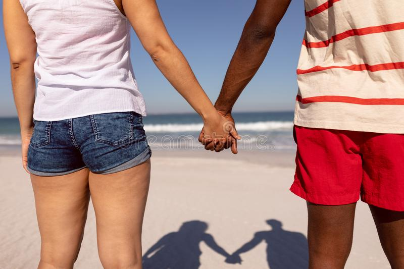 Couple holding hands and standing on beach in the sunshine royalty free stock photos