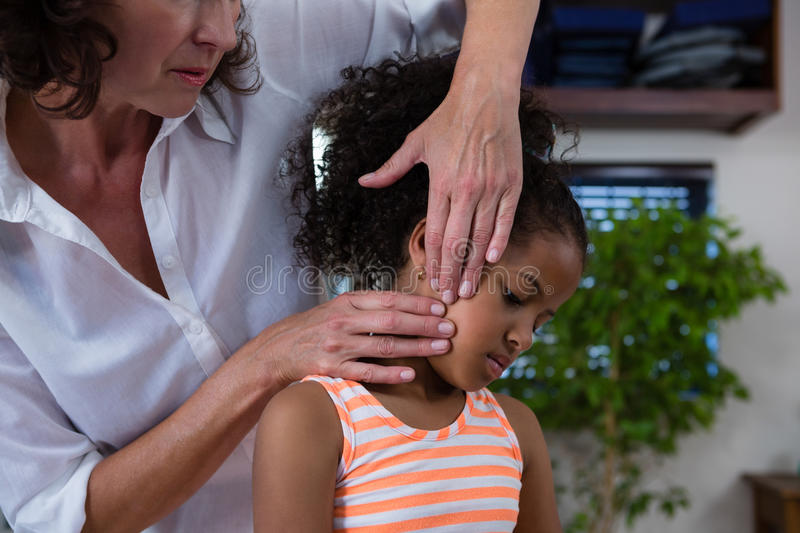 Mid-section of physiotherapist giving neck massage to girl patient. In clinic stock photos