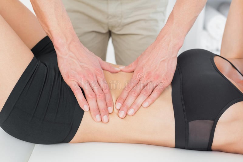 Mid section of a physiotherapist massaging womans body. Closeup mid section of a physiotherapist massaging womans body in the medical office royalty free stock image