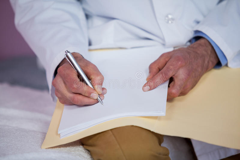Mid section of physiotherapist writing a report royalty free stock image