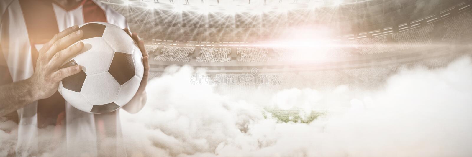 Mid section of player holding football against graphic image of stadium at dusk royalty free stock photography