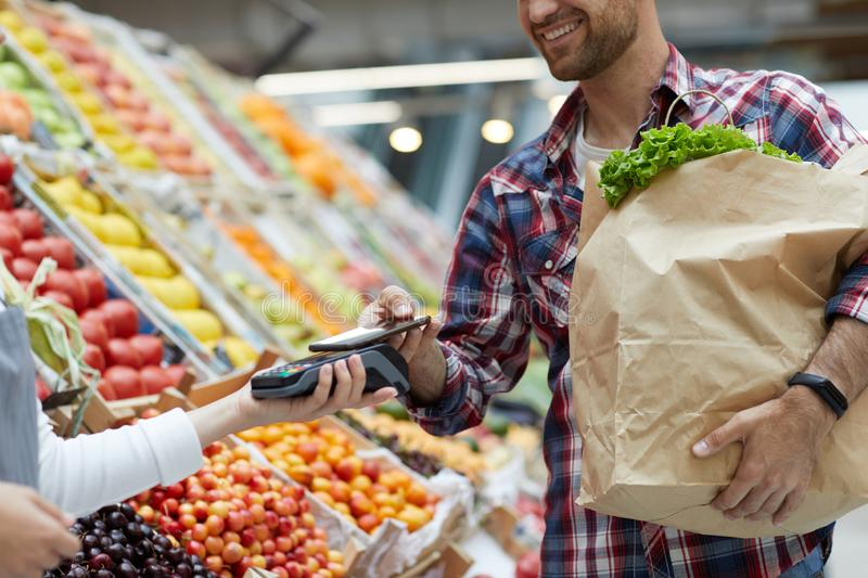 Man Paying by Smartphone in Supermarket. Mid section portrait of smiling young men paying via smartphone at farmers market, copy space royalty free stock photo