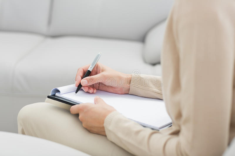 Mid section of a psychologist writing notes royalty free stock images