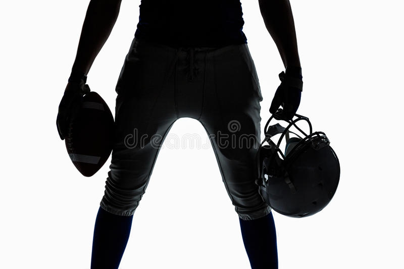 Mid section of silhouette sportsman holding ball and helmet stock photography