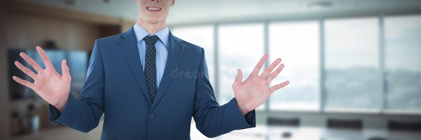 Mid section of smiling businessman using imaginary screen against empty boardroom in office royalty free stock photo