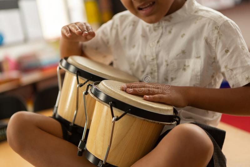 Schoolboy playing bongo in a classroom stock images