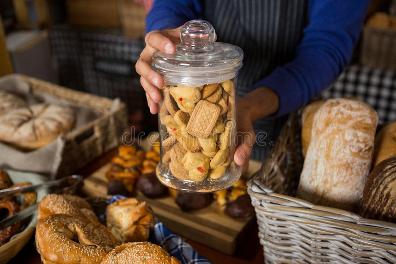 Mid section of staff holding glass jar of cookies at counter. In bakery shop royalty free stock photography