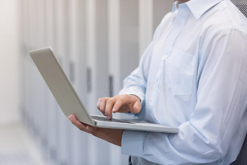 Mid section of a technician typing on his notebook. And leaning against a tower in a large data center royalty free stock photo