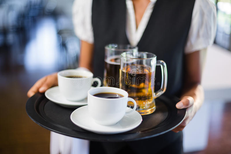 Mid section of waitress holding serving tray with coffee cup and pint of beer. In restaurant royalty free stock photo
