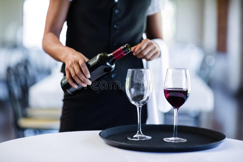 Mid section of waitress pouring red wine in a glass royalty free stock photography