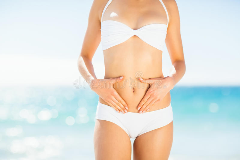 Mid section of woman in bikini touching her belly royalty free stock photography