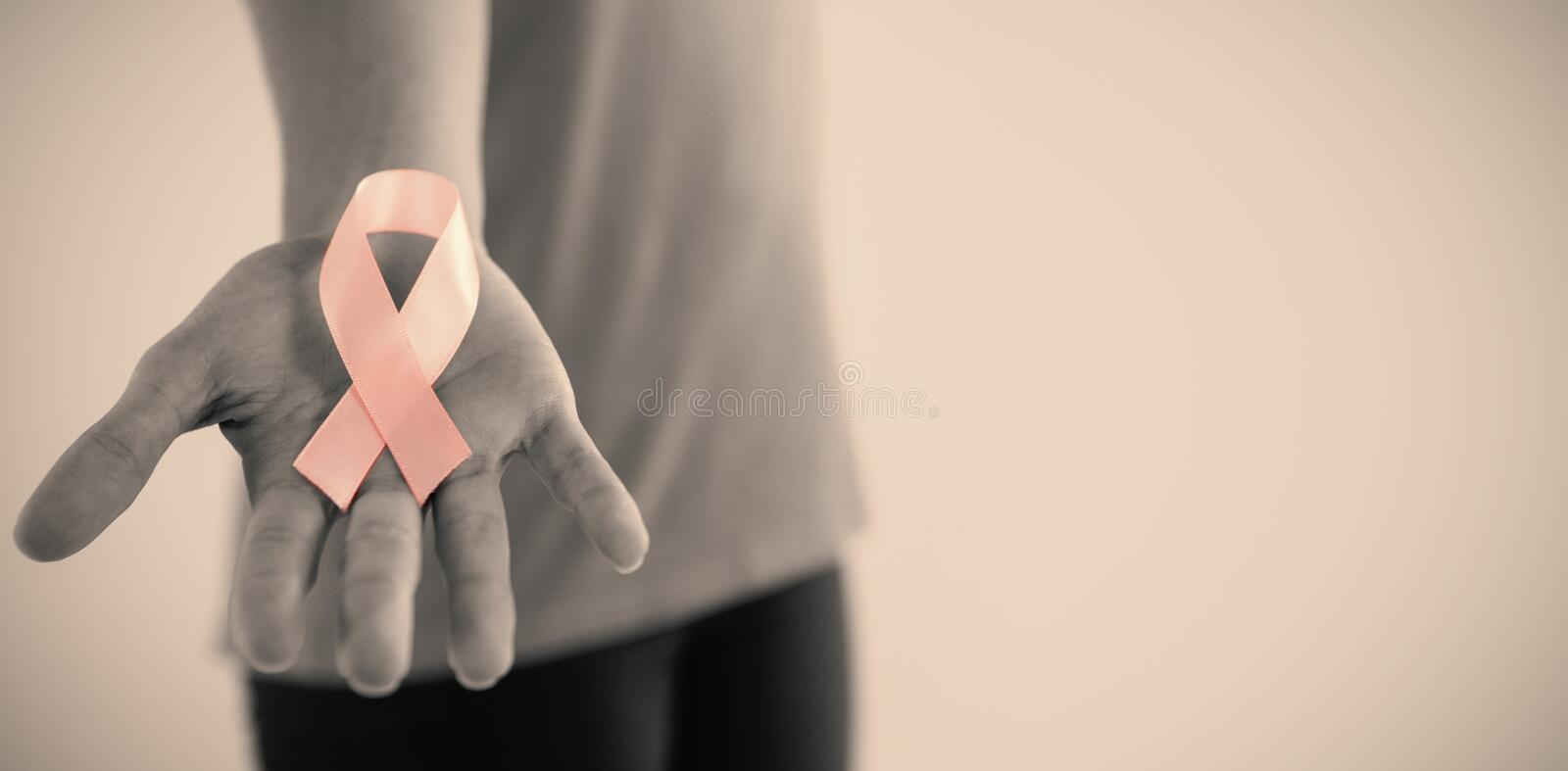 Mid section of woman holding pink breast cancer awareness ribbon. Against gray background royalty free stock image