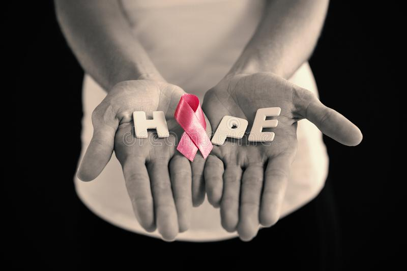 Mid section of woman holding pink ribbon with hope text. While standing against black background royalty free stock images