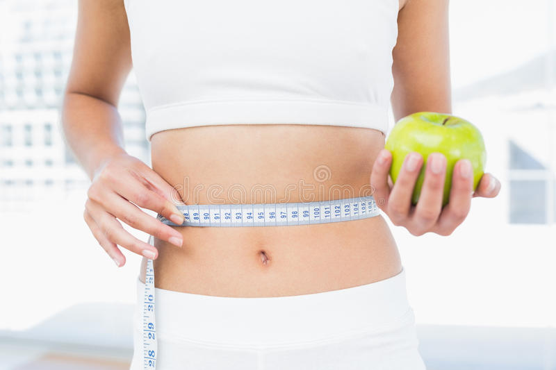 Download Mid Section Of Woman Measuring Waist As She Holds Apple Stock Image - Image of measuring, healthy: 35030507
