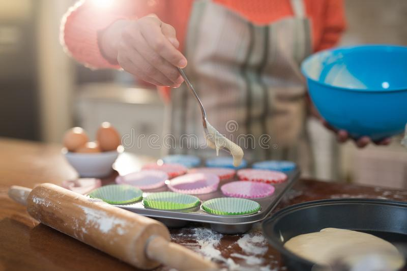 Woman putting muffin batter in paper case in baking tray royalty free stock images