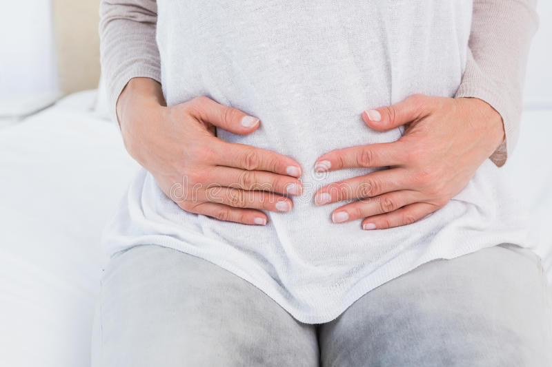 Mid section of woman with stomach pain stock photo