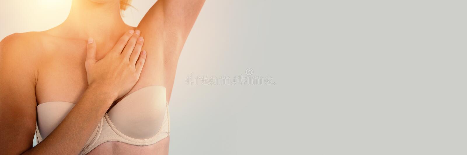 Mid section of woman in strapless bra checking breast royalty free stock photography