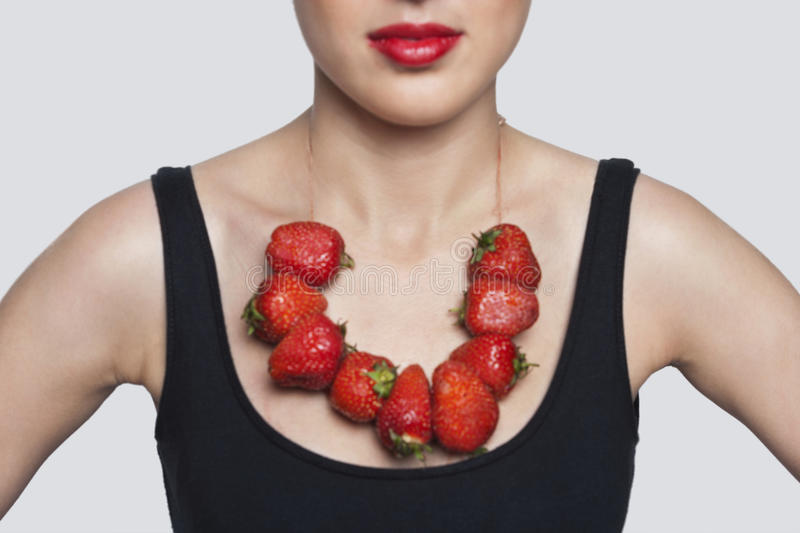 Download Mid Section Of A Woman Wearing Strawberry Necklace Over Gray Background Stock Photo - Image: 30854314