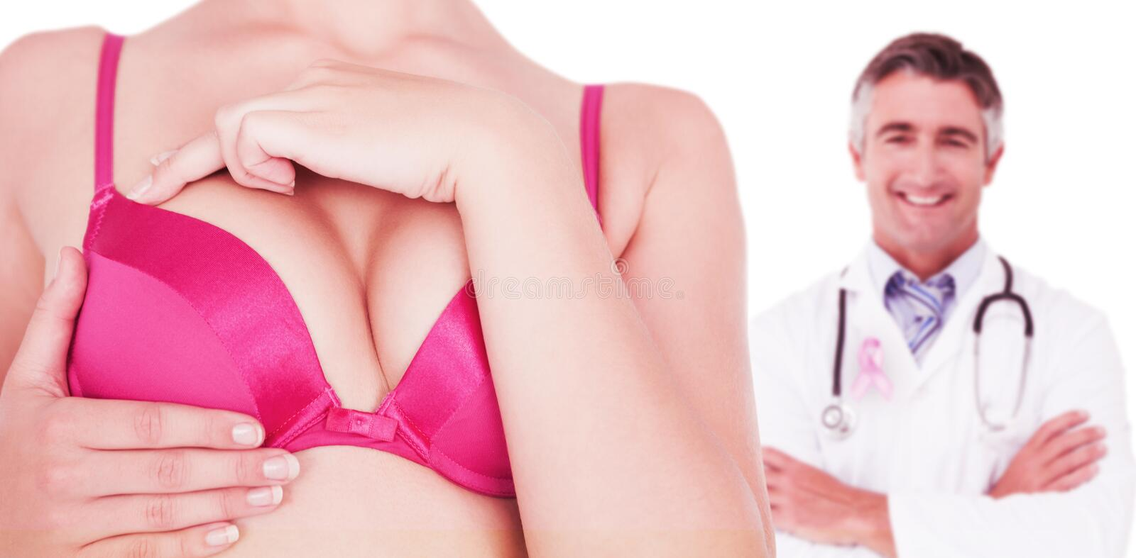 Composite image of mid section of woman in pink bra touching breast for cancer awareness stock photography
