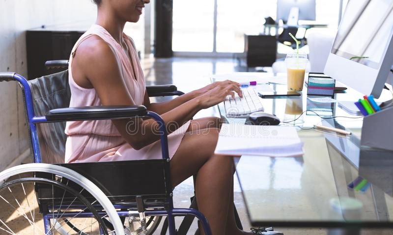 Disabled businesswoman working on computer at desk in the office stock photos