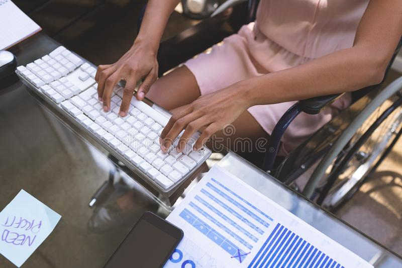 Disabled businesswoman working on computer at desk in the office stock photo