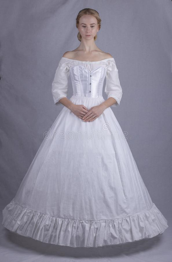 Victorian woman in underwear. Mid-Victorian woman in underwear consisting of a linen chemise, satin corset, cotton petticoat and crinoline stock photography