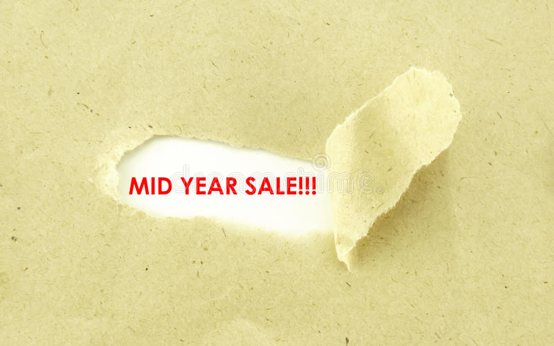 MID YEAR SALE. Text MID YEAR SALE appearing behind torn light brown envelope stock photos