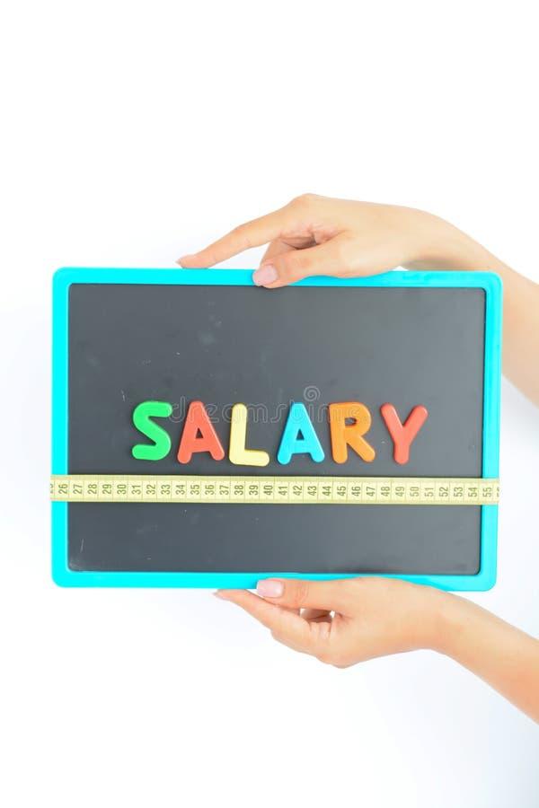 Mida el concepto del sueldo en un negocio, una compañía o una economía fotografía de archivo libre de regalías