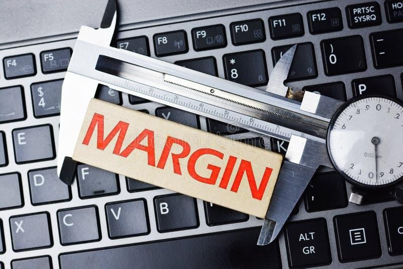 Mida el margen del concepto del beneficio con la herramienta del calibrador en el teclado de ordenador imagen de archivo libre de regalías