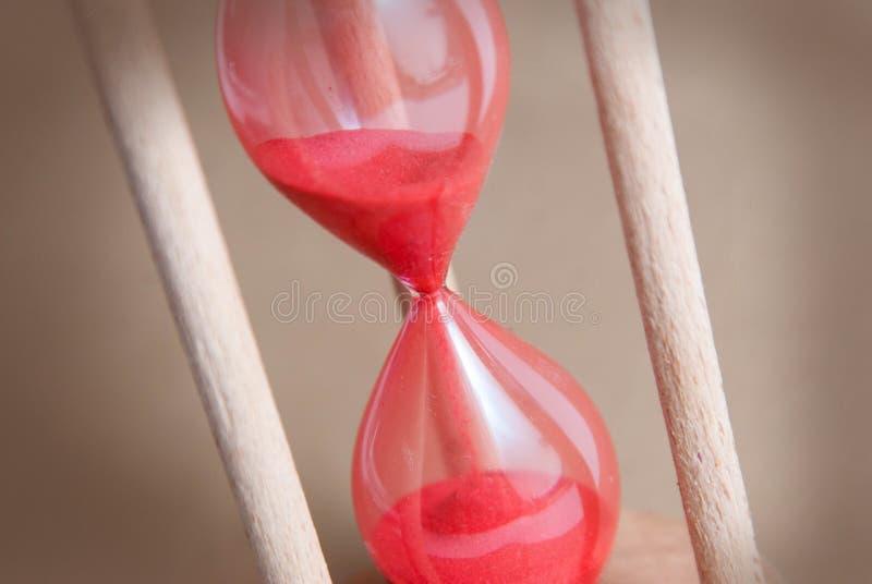 Mida el tiempo del concepto hourglass El ejecutarse de tiempo Sandglass Fondo de marfil neutral Imagen vertical Timmig Backgroun  imagen de archivo libre de regalías