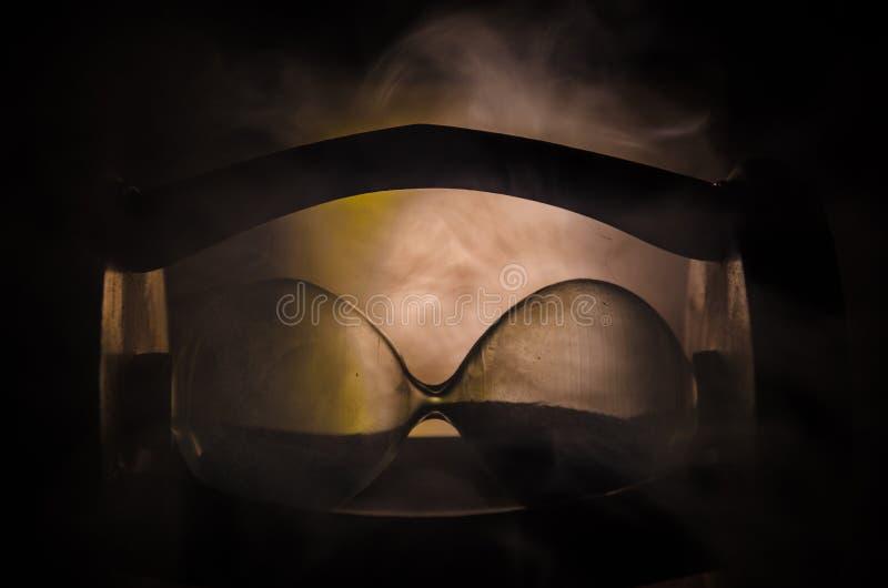 Mida el tiempo del concepto La silueta del reloj del reloj de arena y el humo en fondo oscuro con frío azul rojo amarillo-naranja imagen de archivo