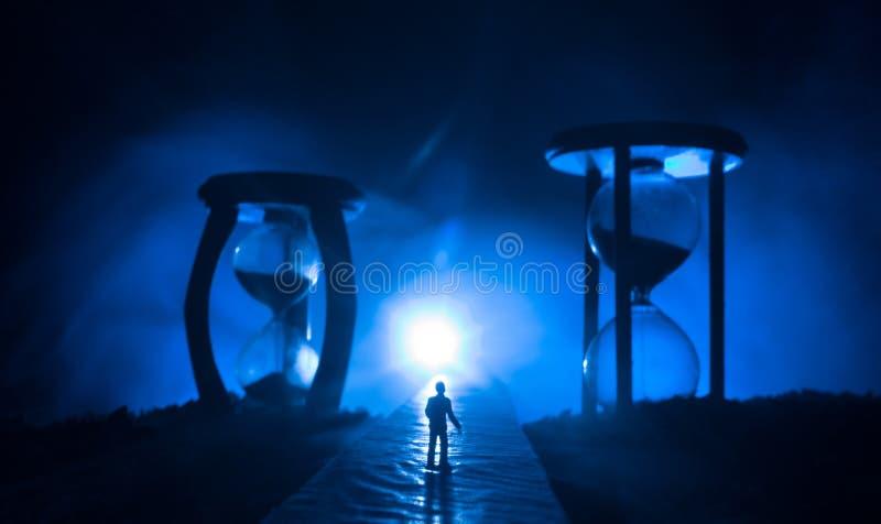 Mida el tiempo del concepto Silueta de un hombre que se coloca entre los relojes de arena con humo y las luces en un fondo oscuro foto de archivo libre de regalías