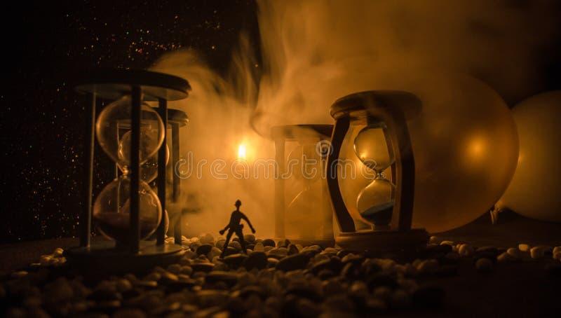 Mida el tiempo del concepto Silueta de un hombre que se coloca entre los relojes de arena con humo y las luces en un fondo oscuro fotos de archivo libres de regalías