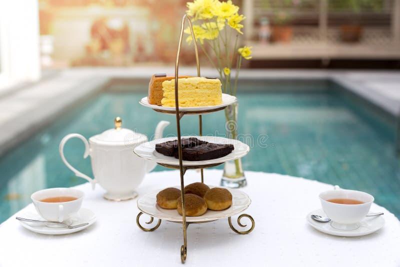 Middagthee met kop thee en theepot op lijst met cake stock fotografie