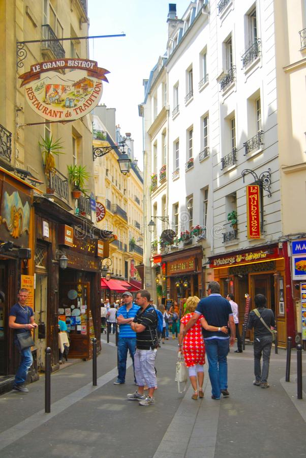 Side streets of Paris with crowd walking leisurely. Midday lunch crowd wanders the side streets of Paris. Lovers embrace arm in arm. Sidewalk cafes fill with the stock image