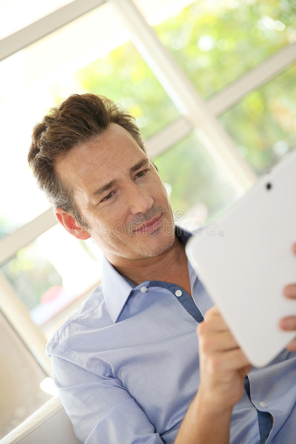 Middel-aged man using a tablet at home. Portrait of middle-aged man at home using tablet stock photos