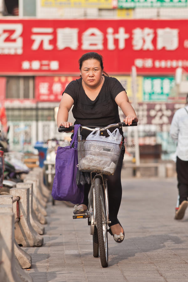 Middel aged woman on a bike in commercial area, Beijing, China. BEIJING-JULY 24, 2015. Middle-aged woman on a bicycle. Although the fast multiplication of cars stock image