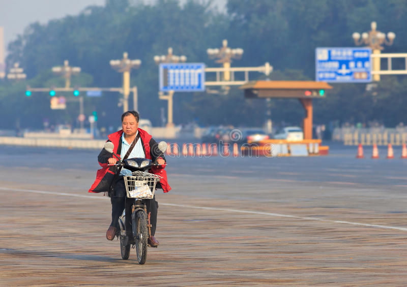 Middel ages man on his e-bike in the early morning, Beijing, China. BEIJING-JUNE 1, 2013. Middle aged man on his electric bike in the early morning. In just a royalty free stock image