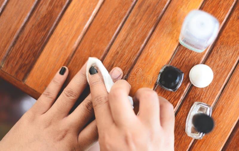 Middel om nagellak te verwijderen - vrouwenhand en het vlekkenmiddel van de spijkervernis met aceton en katoen op houten achtergr stock fotografie