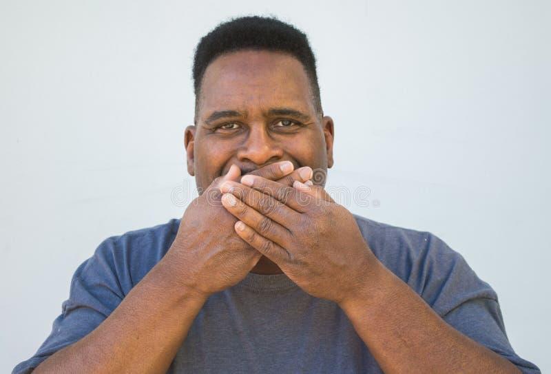 Middel van een midden oude zwarte mens met handen wordt geschoten die zijn mond behandelen die royalty-vrije stock afbeelding