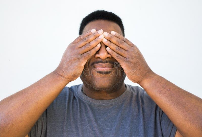 Middel van een midden oude zwarte mens met handen wordt geschoten die zijn ogen behandelen dat stock fotografie