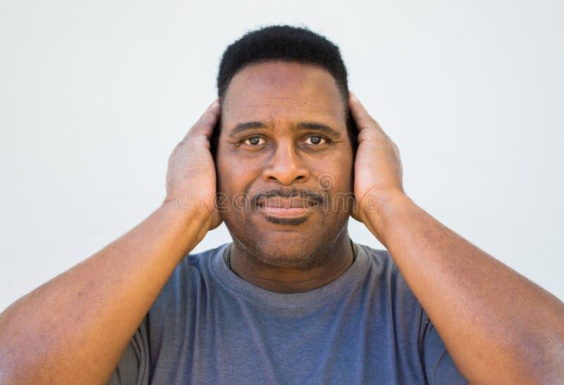 Middel van een midden oude zwarte mens met handen wordt geschoten die zijn oren behandelen dat stock foto's