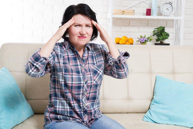 Middelbare leeftijd Vrouw die hoofdpijn heeft en stress die haar handen vasthoudt aan haar tempels met haar ogen die in pijn zijn royalty-vrije stock afbeeldingen