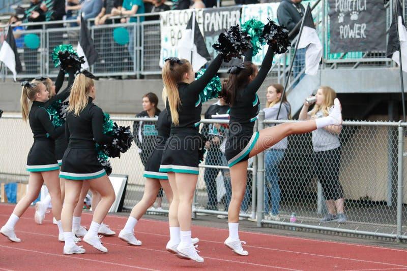 Middelbare school Cheerleaders bij een Voetbalspel royalty-vrije stock afbeeldingen