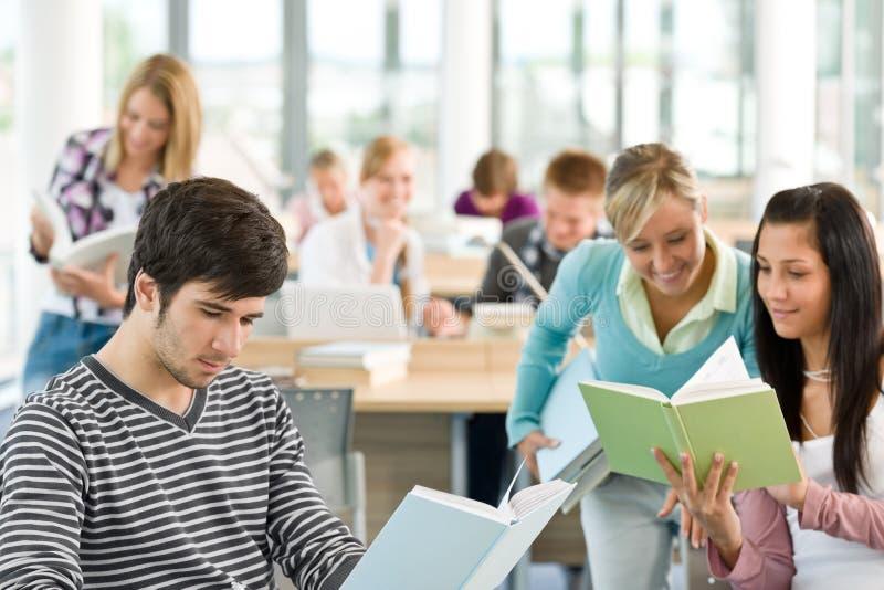 Middelbare school - drie studenten met boek stock afbeeldingen